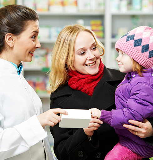 Young mother holding her baby while friendly Best Value Pharmacies representive interacts.